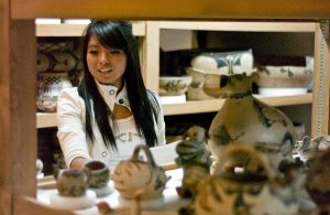 Merlinda Coriz (Santo Domingo) examines pottery in the IARC collections during a class visit