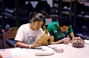 Shaylene Platero (Navajo) and Mathew Naranjo (Santa Clara Pueblo) in a hands-on examination of the IARC pottery