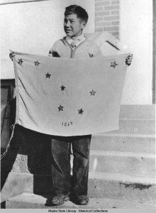 Benny Benson holding the Alaska State Flag